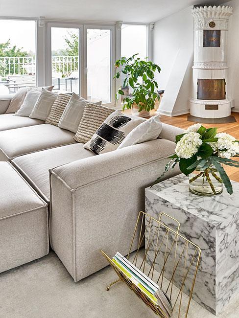 Jasny salon z szarą sofą i kominkiem kaflowym w tle
