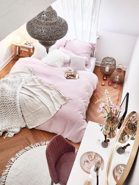 Pomysły na ciepłe kolory w sypialni - różowa kołdra, bordowe krzesło, drewniana podłoga