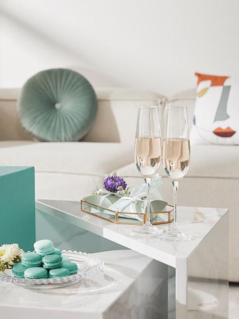 Dwa kieliszki szampana na trójkątnym stoliku z marmuru na tle jasnej sofy z seledynową poduszką