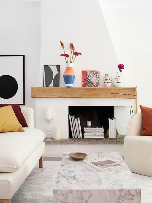 Biały kominek z drewnianą półką w jasnym salonie z kolorowymi geometrycznymi dekoracjami