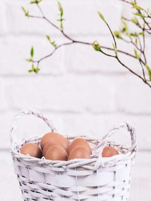 Biały koszyczek z jajkami na stole obok wazonu z gałązką