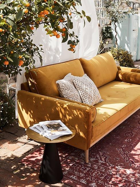 żółta sofa z aksamitu na bordowym orientalnym dywanie obok złotego stolika
