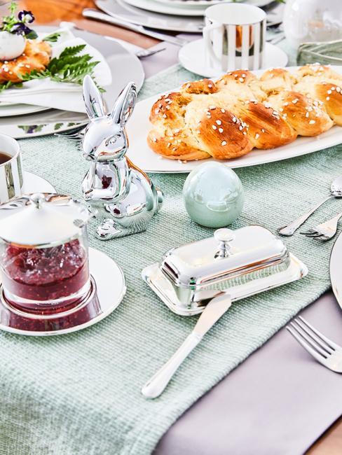 Zbliżenie na stół udekorowany na Wielkanoc - pastelowym obrusem, figurką zajączka i pisanką