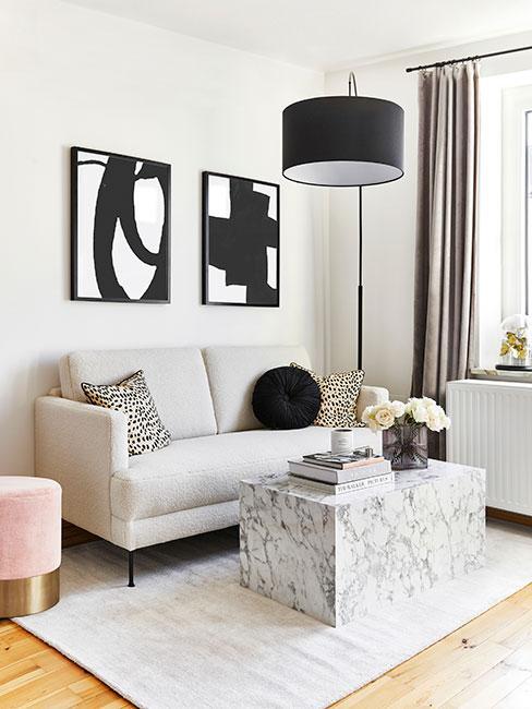 Maly jasny salon z popielatą sofą z aksamitu, marmurowaym stolikiem i różowym pufem