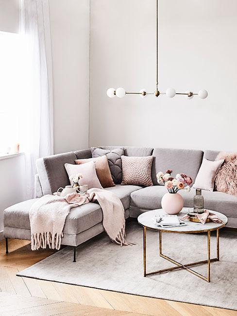 Jasny salon z szarobeżową sofą i jasnoróżowymi poduszkami
