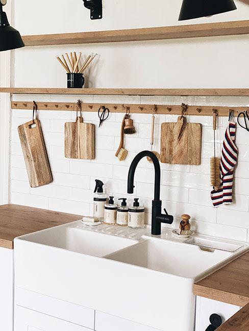 Kuchnia z drewnianym blatem, dużym, dwokomorowym zlewem oraz drewnianymi półkami, na których są zawieszone akcesoria