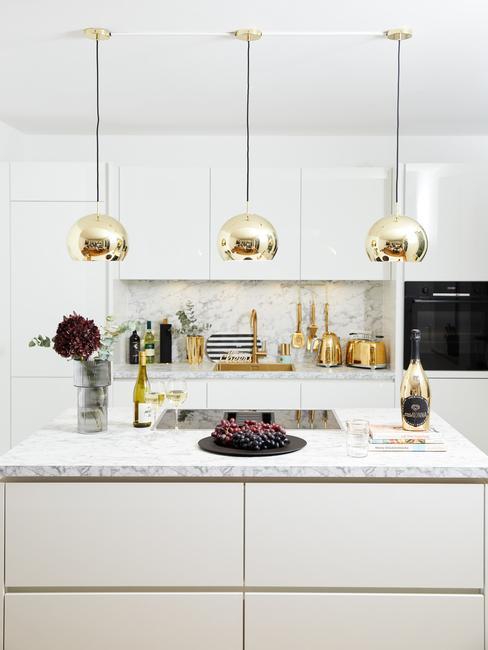 Biała kuchnia z minimalistycznymi frontami szafek, złotymi lampami, wyspą kuchenną i dekoracjami