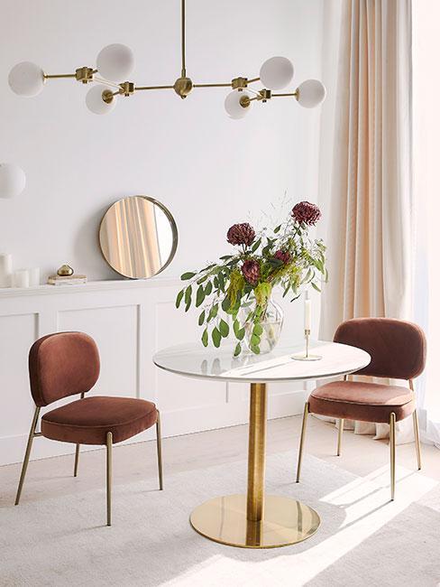 Biały okrągły stół do jadalni obok aksamitnych krzeseł w kolorze terakoty w jasnym salonie na tle białej komody