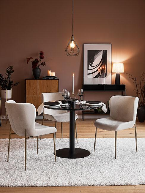 ciemny stół do jadalni obok jasnych krzeseł z aksamitu na tle ściany w kolorze zgaszonego różu