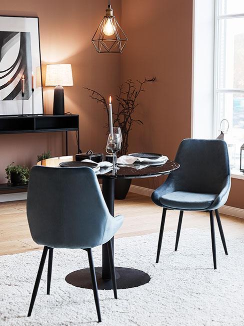 Przytulny kącik jadalniany z okrągłym czarnym stołem, niebieskimi tapicerowanymi krzesłami na tle ściany w kolorze karmelu
