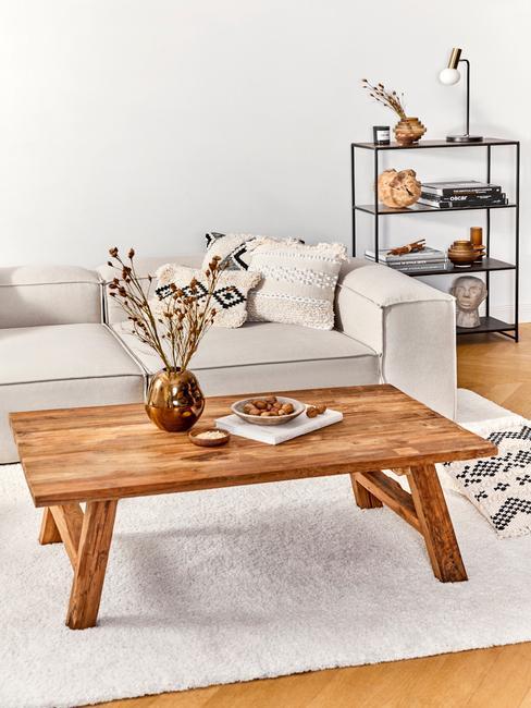 Biały salon z białą sofą, drewnianym stołem z wazonem oraz czarną, metalową półką