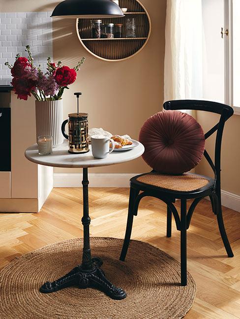 Stoliczek przy ciemnym drewnianym krześle i zaparzoną kawą