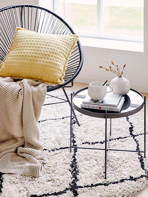 Czarny ażurowy fotel na puszystym dywanie obok małego okrągłego czarnego stolika