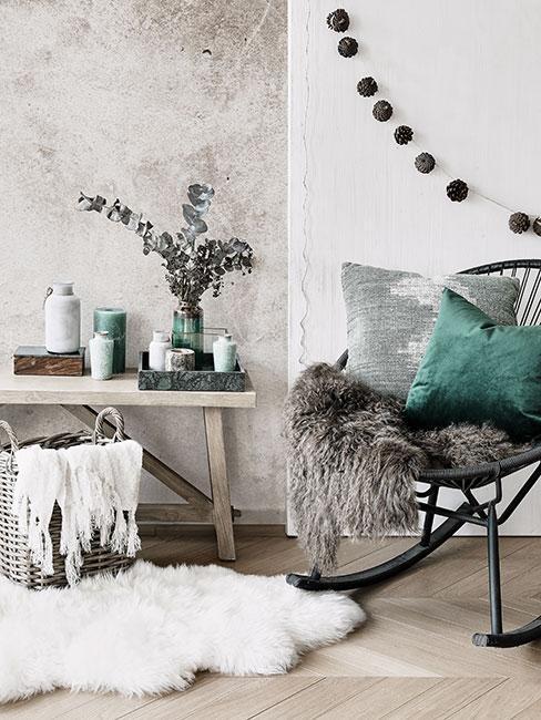 Przytulny kącik z fotelem bujanym i zieloną poduszką i szarym futerkiem obok drewnianego stolika