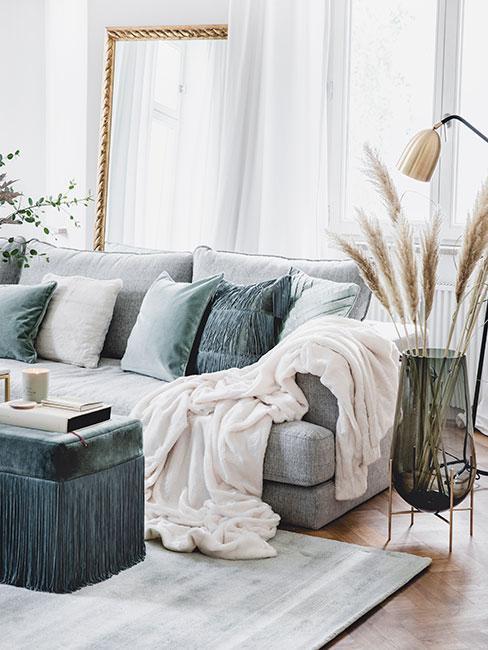 salon w stylu glamour z szarą sofą i poduszkami i pufą w kolorze szałwiowym