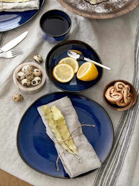 Zbliżenie na niebieski talerz ze złotą dekoracją na lnianym obrusie