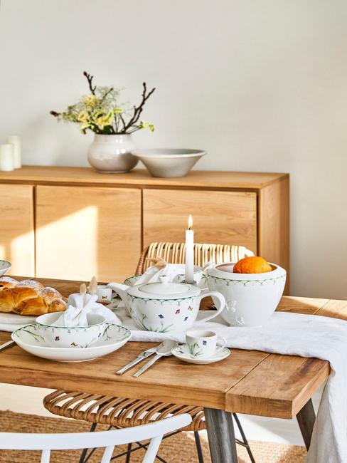 Jadalnia z drewnianą komodą oraz stołem, na której znajduje się zastawa we wzory kwiatowe