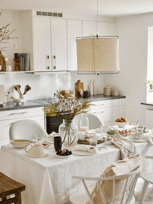 Stół w białej kuchni, nakryty obrusem oraz białą zastawa i dekoracjami na Wielkanoc
