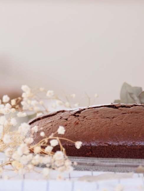 Ciasto czekoladowe na lnianej ściereczce, obok suszonych kwiatów