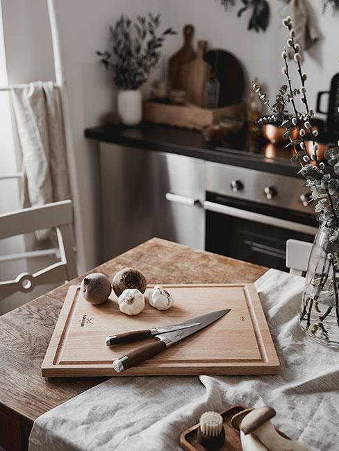 Zbliżenie na drewnianą deskę do krojenia z ząbkami czosnku w kuchni z drewna w stylu rustykalnym