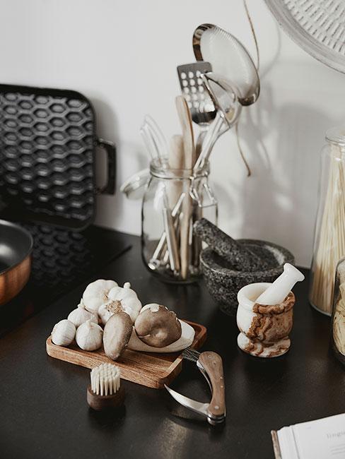 Zbliżenie na drewnianą deskę do krojenia z ząbkami czosnku w ciemnej kuchni w stylu rustykalnym