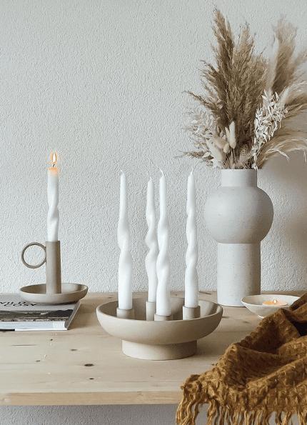 Białe świece ze skrętem w jasnym świeczniku z kamienia na beżowej komodzie w stylu boho