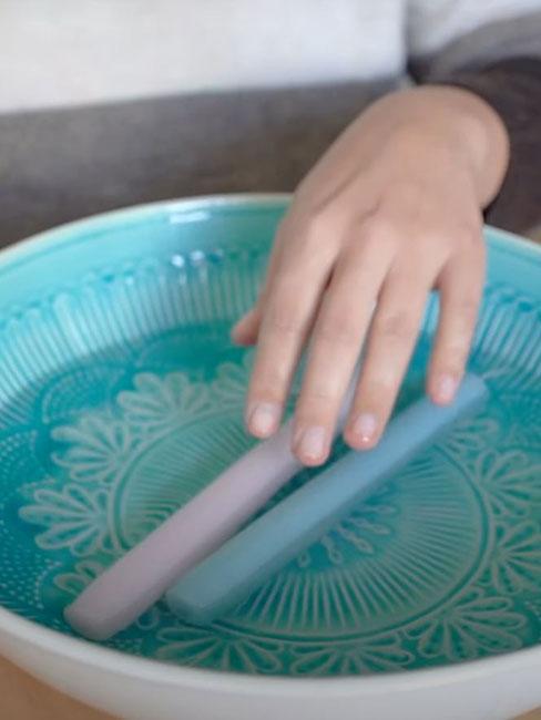 Głęboka niebieska miska z wodą, w której są świece