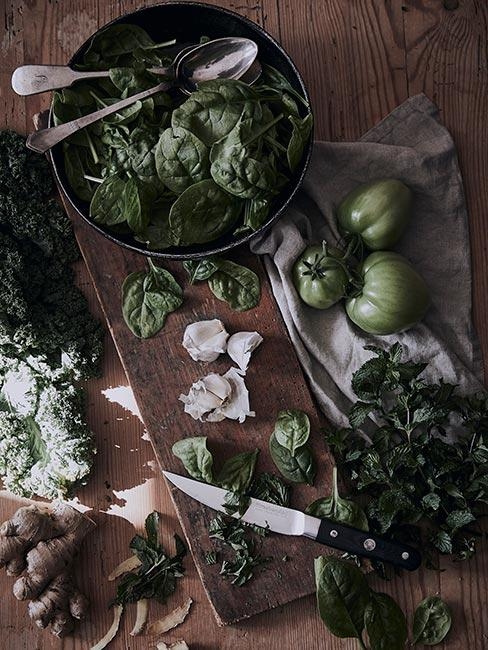 Zieloone pomidory i bazylia w naczyniach i desce kuchennej
