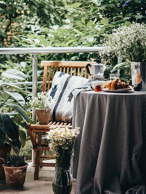 Mały balkon w zieleni z drewnianym krzesłem i nakrytym stoliczkiem z kawiarką i rogalikiem