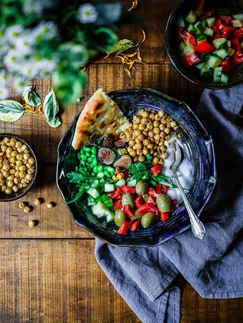 Kolorowe danie wegańskie z ciecierzycą, warzywami i podpłomykiem
