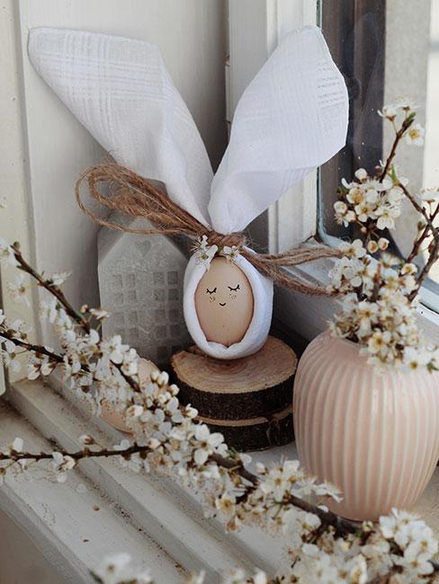jajko z rysunkową twarzą owinięte białą lnianą serwetką na parapecie obok kwitnących gałązek jabłoni