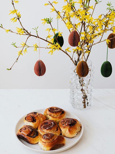 drożdżówki cynamonowe obok wazonu z gałązkami forsycji, udekorowanych paiperowymi jajkami
