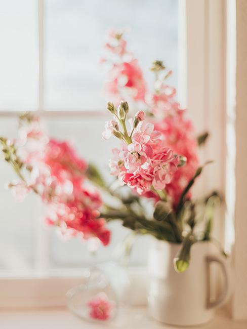 Piękne różowe kwiaty na parapecie w białym wazonie