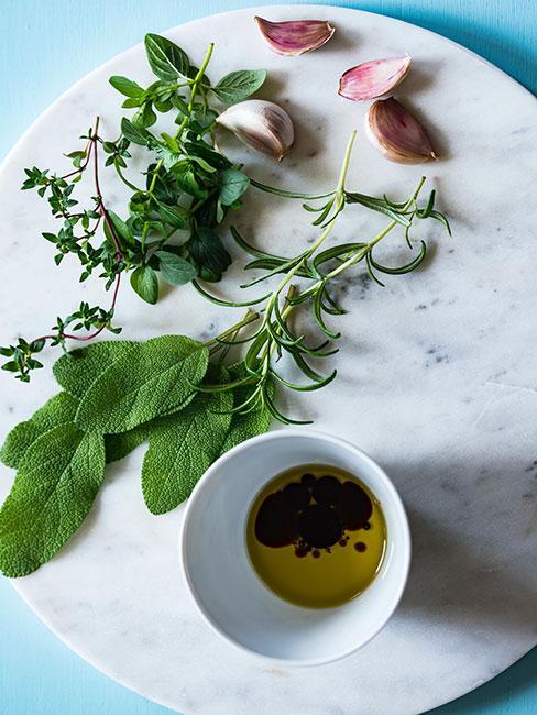 zioła i ząbki czosnku na marmurowej tacy obok naczynia z oliwą i octem