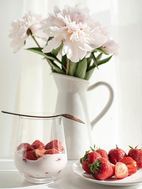Truskawki z jogurtem w pucharku na stole obok wazonu z białymi kwiatami