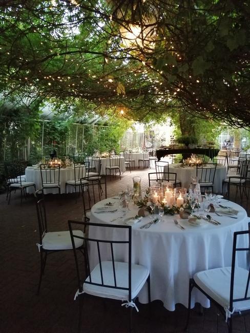 romantyczne białe stoliki przy metalowych krzesłach pod pergolą przygotowane na przyjęcie weselne