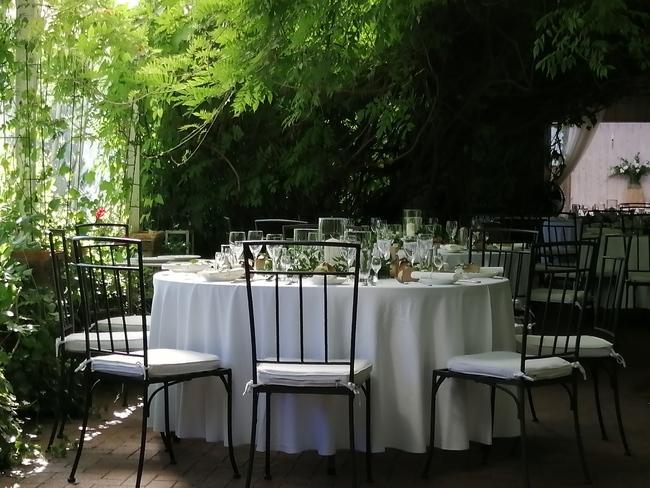 okrągłey stół nakryty białym obrusem przy metalowych krzesłach w ogrodzie