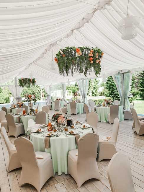 okrągłe stoły nakryte białymi obrusami przy beżowych tapicerowanych krzesłach pod namiotem weselnym w ogrodzie