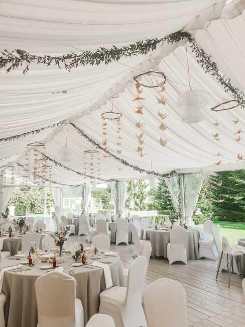 okrągłe stoły nakryte szarymi obrusami pod namiotem weselnym w ogrodzie