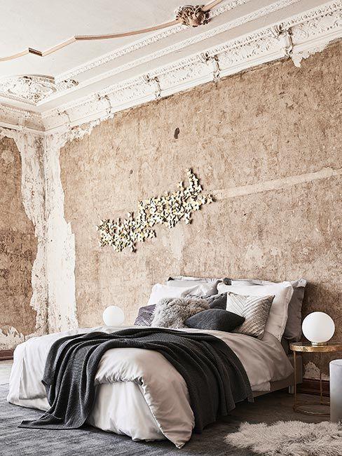 Sypialnia z surową betonową ścianą i dekoracyjną sztukaterią