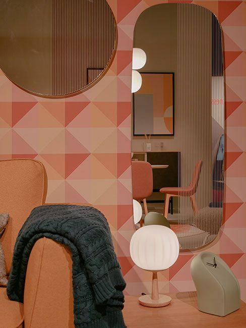 Różnokształtne lustra wiszące na fantazyjnej tapecie w odcieniach różu
