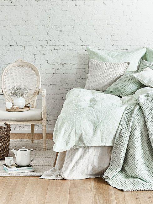 Sypialnia z zielonkawą pościelą i bieloną ścianą z cegły