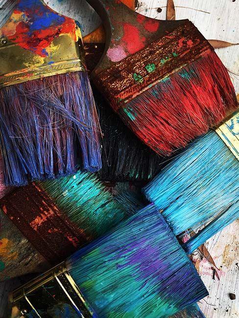 Pędzle pobrudzone kolorowymi farbami