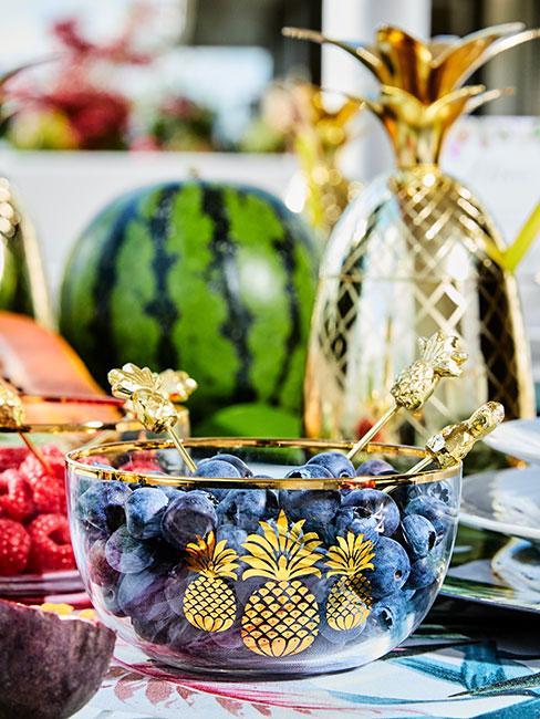 Zbliżenie na borówni amerykańskie w szklanej miseczce ze złotym obramowaniem wśród innych kolorowych owoców na stole