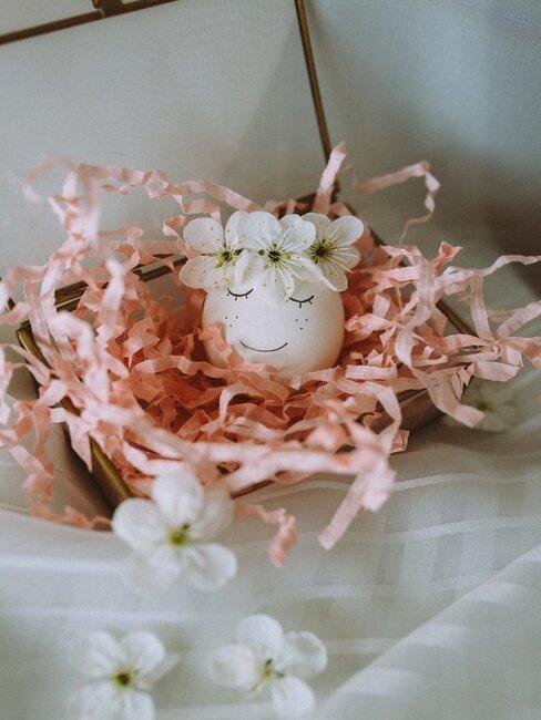 Pisanka w kwiatowym wiankiem otoczona papierowymi ścinkami