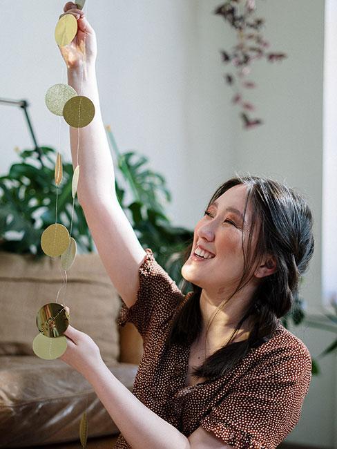 Kobieta robiąca złotą girlandę z papieru