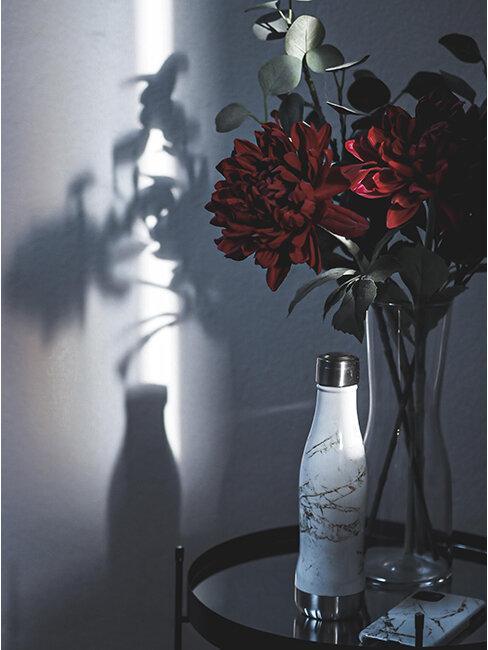 Butelka na wodę stojąca obok wazonu