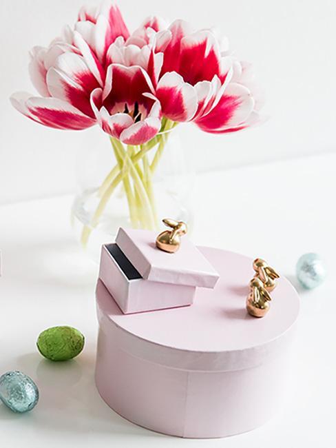 Okrągłe różowe pudełka na prezenty ozdobione złotymi zajączkami