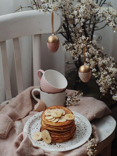 Naleśniki na białym krześle obok strokia z gałązek jabłoni udekorowanymi pozłacanymi pisankami