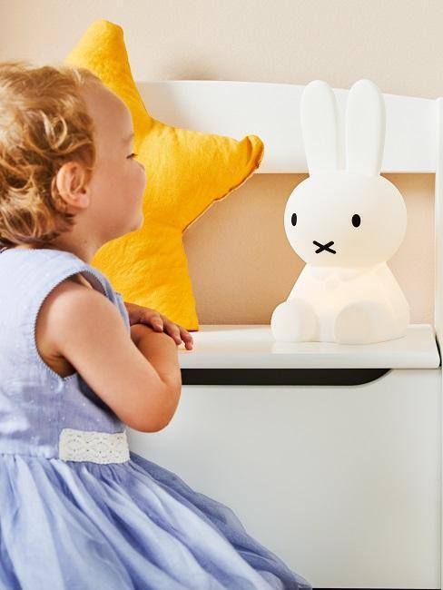 Mała dziewczynka obok lampy w kształcie królika